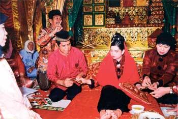 Pengantin perlu sabar menanti inai yang dipakai itu terus merah di kaki dan tangan. Imej dari Melayu Online.